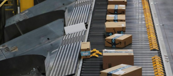 Amazon packages are pushed onto ramps leading to delivery trucks by a robotic system as they travel on conveyor belts inside of an Amazon fulfillment center on Cyber Monday in Robbinsville, New Jersey