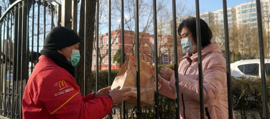 McDonald's delivery worker wearing a face mask passes food to a resident through a fence at a residential compound, as the country is hit by a novel coronavirus outbreak in Beijing